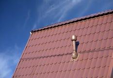 Крыша дома покрытого с плиткой металла с печной трубой Стоковые Фотографии RF