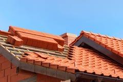 Крыша под конструкцией с стогами красных керамических черепиц готовых для закрепления Стоковые Изображения