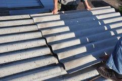Крыша ремонта Roofers и извлечь черепицы азбеста старые Конструкция толя стоковые изображения