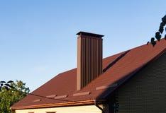 Крыша с камином сделанным коричневый профилированный покрывать, закрывает вверх стоковая фотография rf