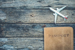 Крышка и самолет пасспорта на деревенской деревянной предпосылке таблицы, перемещении Стоковые Изображения