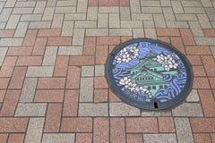 Крышка люка в Осака, Японии Замок и Сакура Осака стоковое фото
