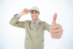 Крышка работника доставляющего покупки на дом нося пока показывающ жестами большие пальцы руки вверх Стоковые Фото