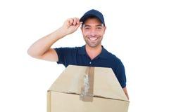 Крышка счастливого работника доставляющего покупки на дом нося пока держащ картонную коробку Стоковые Изображения