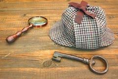 Крышка Sherlock Holmes известная как Deerstalker, старый ключ и увеличитель Стоковое Изображение RF