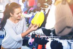 Крышки knit женского клиента рассматривая в магазине спорт Стоковые Фотографии RF