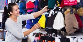 Крышки knit женского клиента рассматривая в магазине спорт Стоковая Фотография