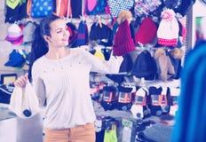 Крышки knit женского клиента рассматривая в магазине спорт Стоковое Изображение