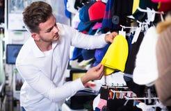 Крышки knit мужского клиента рассматривая в магазине спорт Стоковая Фотография