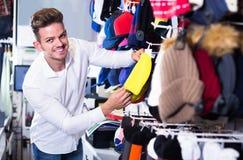 Крышки knit мужского клиента рассматривая в магазине спорт Стоковое фото RF