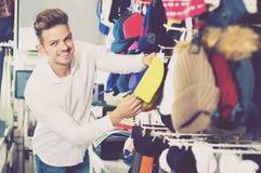 Крышки knit мужского клиента рассматривая в магазине спорт Стоковое Изображение RF