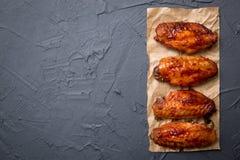 Крыла жареной курицы на темноте - серая предпосылка Стоковое Фото