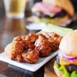 Крыла и гамбургеры барбекю бескостные Стоковая Фотография