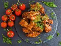 Крыла цыпленка сварили с соусом барбекю на черной каменной предпосылке Малые томаты вишни и укроп Взгляд сверху Стоковое Изображение RF