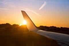 Крыло двигателя самолета на заходе солнца с золотым солнечным светом Стоковые Фотографии RF