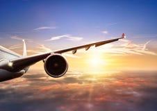 Крыло летания самолета над облаками в свете захода солнца Стоковые Фото