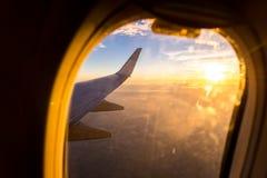 Крыло самолета воздуха на море предпосылки неба захода солнца облаков Стоковое Изображение