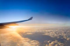 Крыло самолета воздуха на море предпосылки неба захода солнца облаков Стоковые Фото