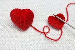 Крюк вязания крючком и предпосылка яркого, красочного красного вязания крючком handmade с сердцем вязания крючком Фото вязания кр Стоковая Фотография