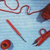 Крюк вязания крючком, ножницы, пряжа и шерстяной шарик на вязать крючком крючком ткани Стоковые Изображения RF