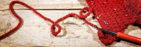 Крюк знамени, вязания крючком и красные шарф, дело рук и мода Стоковые Изображения