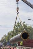 Крюк крана поднимая массивнейшую стальную трубу Стоковые Фотографии RF