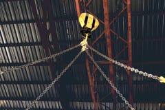 Крюк крана с цепями приостанавливанными к нему стоковые фотографии rf