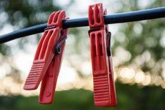 Крюк яркого цвета зажимки для белья красный на кабеле Стоковые Изображения
