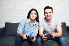 Кто выиграет Конкуренция отпрысков играя автогонки Excited друзья играют игры внутри помещения дома, сидящ на уютном беже Стоковое Изображение RF