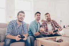 Кто выиграет? Конкуренция парней играя автогонки Excited frie стоковое изображение rf