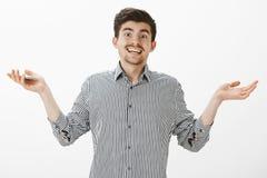 Кто заботит что случитесь Портрет халатной равнодушной привлекательной мужской модели в серой рубашке, распространенных ладонях и стоковые изображения