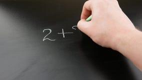 Кто-то рука белит на классн классном математический пример мелом для детей Назад к концепции школы сток-видео