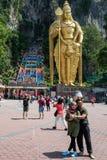 Куала-Лумпур, Малайзия - 26-ое февраля 2019: Туристы делают фото перед статуей лорда Murugan на пещерах Kuala Batu стоковое изображение rf
