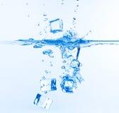 Кубики льда упали в воду с выплеском Стоковое Фото