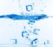 Кубики льда упали в воду с выплеском стоковые изображения rf