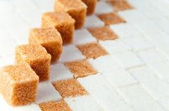 Кубики уточненного камышового и белого сахара стоковое изображение