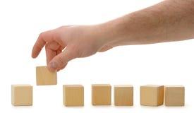 кубик устанавливает рядок руки деревянный стоковое фото