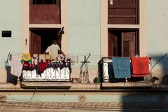 Кубинец на балконе старого дома Испанск-стиля на предпосылке старого балкона стоковая фотография