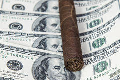 Кубинськая сигара на долларах стоковое фото