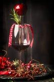 Кубок красного вина с праздничным украшением рождества и розмаринового масла на темной деревенской деревянной предпосылке Стоковое Изображение
