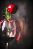 Кубок красного вина с украшением рождества и розмаринового масла на темной деревенской деревянной предпосылке Стоковое Изображение