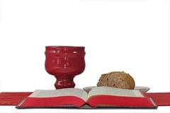 Кубок, хлеб и библия на белой предпосылке Стоковое Фото