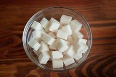 Кубы белого сахара в стеклянном шаре на деревянном столе Стоковая Фотография
