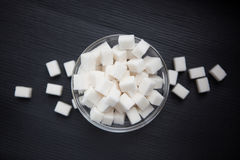 Кубы белого сахара в центре черной предпосылки Стоковая Фотография