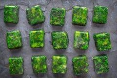 Кубы замороженного шпината на каменном взгляде столешницы Стоковая Фотография