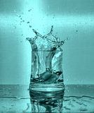 Кубы льда брызгая в стекло воды стоковые изображения rf