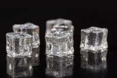 Кубы льда с падениями воды на черной предпосылке с отражениями Стоковые Изображения RF