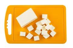 Кубы сыра фета на оранжевой пластичной разделочной доске Стоковые Фотографии RF