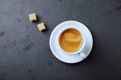 Кубы чашки кофе и желтого сахарного песка на черной каменной предпосылке стоковая фотография