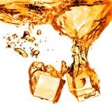Кубы льда упали в оранжевую воду при выплеск изолированный на whit Стоковое Фото